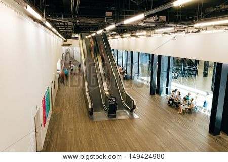 LONDON UK - AUGUST 22 2015: High angle view of escalators in Tate Modern Art Gallery interior. With people blurred moving