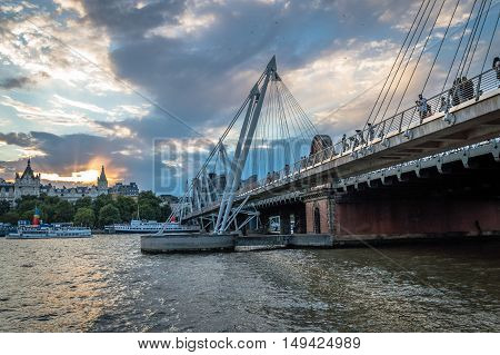 LONDON UK - AUGUST 22 2015: London Eye and Hungerford Bridge and Golden Jubilee Bridges from the river at sunset