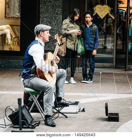LONDON UK - AUGUST 20 2015: Street musician plays acoustic guitar near the entrance of Harrods while some people are listening. Dozens buskers perform on the streets of London.