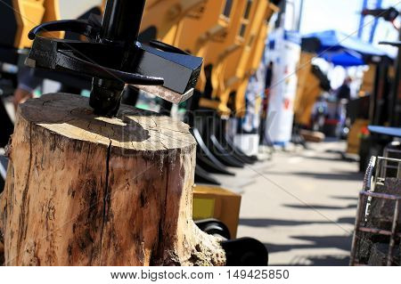 Woodworking, old stump in the background of construction machinery