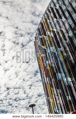 London UK - August 19 2015: Modern office building in London with a colorful facade of glass. Low angle view