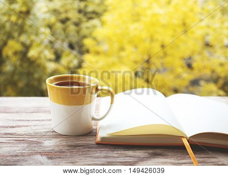 Cup of tea with book on the wood background