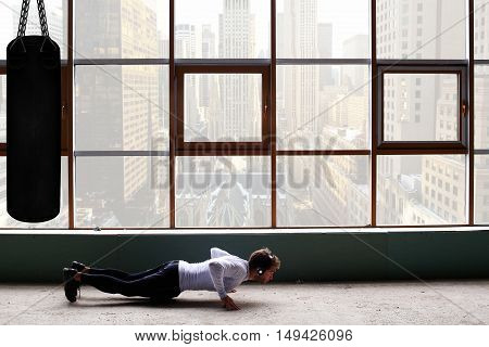 Man with headphones training on the background of window