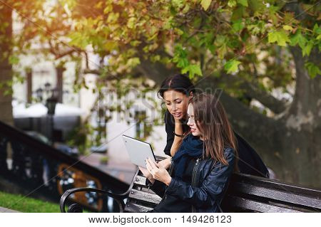 two beautiful young girls , look at the photos on your tablet , socializing on the Internet