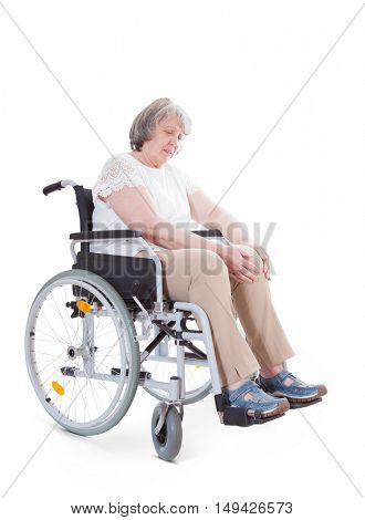 Senior sitting in wheelchair suffers from knee pain. All on white background.