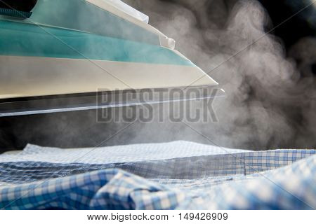 Iron With Steam Over Blue  Shirt