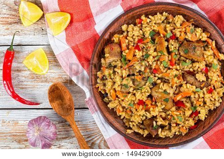 paella with meat pepper vegetables and spices on clay dish kitchen towellemon slice garlic chili pepper and wooden spoon on white peeling paint planks view from above