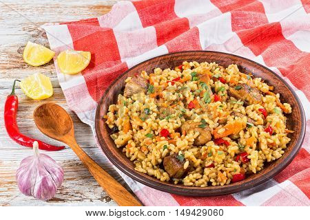 rice with meat pepper vegetables and spices on clay dish kitchen towellemon slice garlic chili pepper and wooden spoon on white peeling paint planks view from above close-up