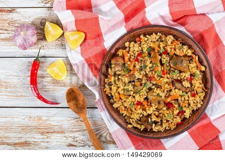 rice with meat pepper vegetables and spices on dish lemon slice garlic chili pepper and wooden spoon on white peeling paint planks view from above