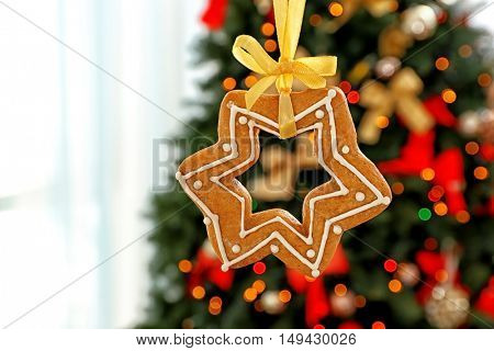 Delicious Christmas cookie hanging against blurred fir tree background