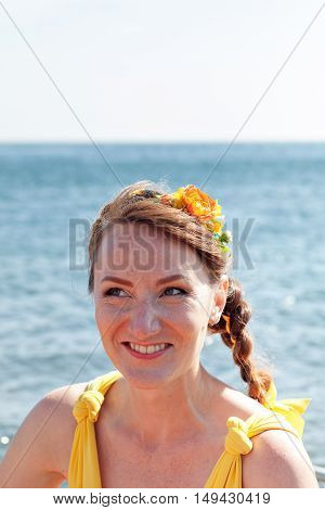Young beautiful girl bride in a bright orange dress. Summer bouquet in hands of the bride. Decoration of flowers in their hair hairstyle. Hippie Bride on the shore of Lake Baikal.