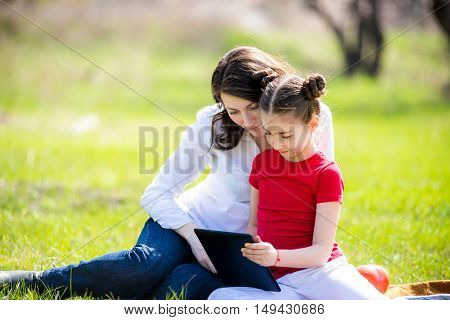 Mother and daughter using digital tablet while sitting in the beautiful nature