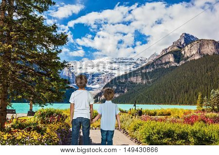 Two lovely slender boys admire the beauty of the glacial lake. Lake Louise  in Banff National Park in the Canadian Rockies