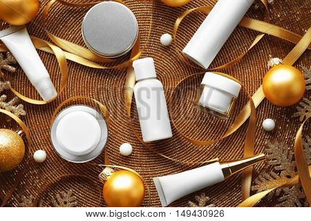 Beauty cosmetic products with Christmas decoration on golden beaded mat background