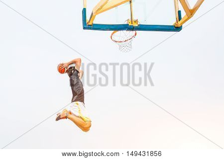 Performance of a white basketball player on the outdoor field in the city road