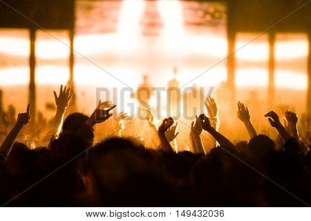 De-focused concert crowd with a raised hand