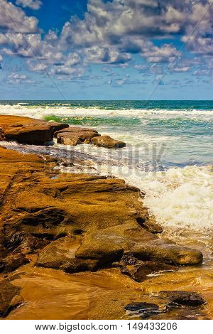 The Pacific waves splash on the rocks of a beach in Caloundra Queensland Australia.