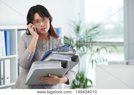 Asian female entrepreneur wit many folders talking on phone