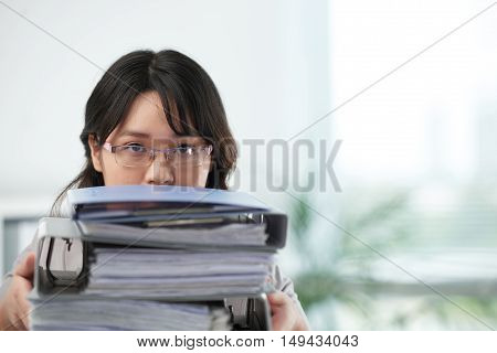 Face of business woman looking out of big stack of folders