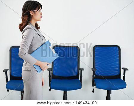 Vietnamese business woman with folder walking along office corridor
