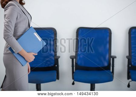 Cropped image of female business executive walking along row of chairs