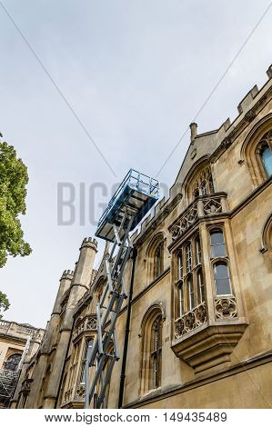 Telescopic boom lift at an old public building. Low angle view.