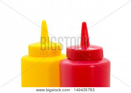 Top of a ketchup in the back and ketchup bottle in the front closeup isolated on white