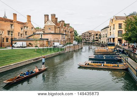 CAMBRIDGE UK - AUGUST 11 2015: Punting on the river Cam. Some companies and students hire punts to visitors and tourists. Cambridge is a university city and one of the top universities in the world.