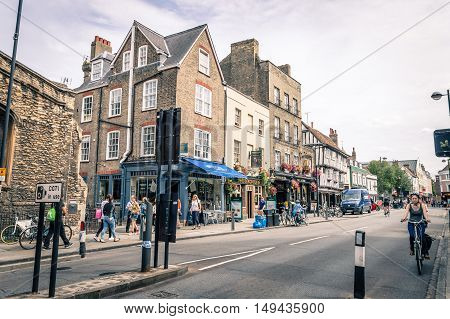 CAMBRIDGE UK - AUGUST 11 2015: Young woman in a Bicycle in a Street in Cambridge. Cambridge is a university city and one of the top five universities in the world.