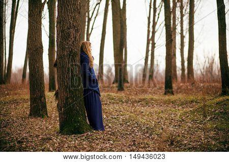 Lonely woman standing in forest in winter.