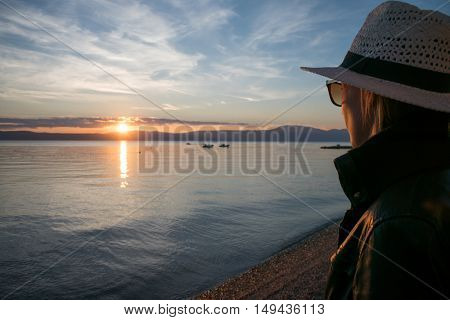 Young woman watching sunset over the sea