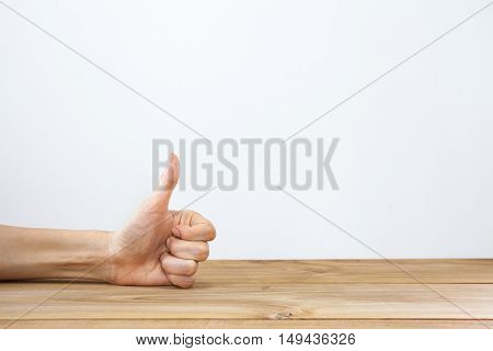 A hand showing thumbs up gesture on a white background