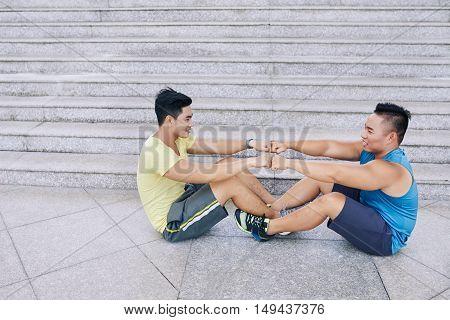 Sportsmen enjoying working on abdominal muscules outdoors
