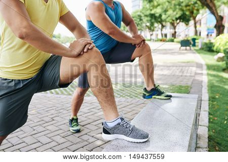 Cropped image of sporty people doing lunges in city park