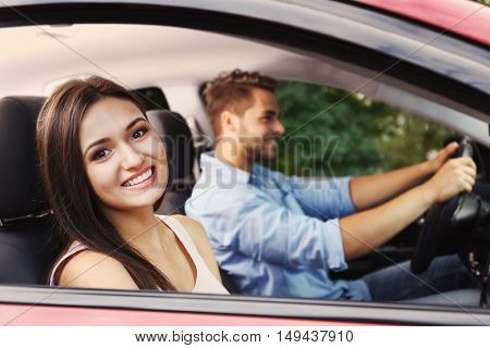 Beautiful young woman looking out of open car window