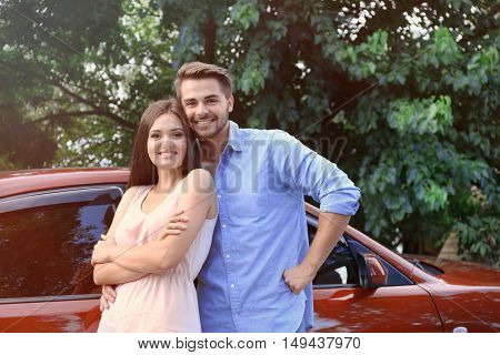Beautiful young couple standing near red car