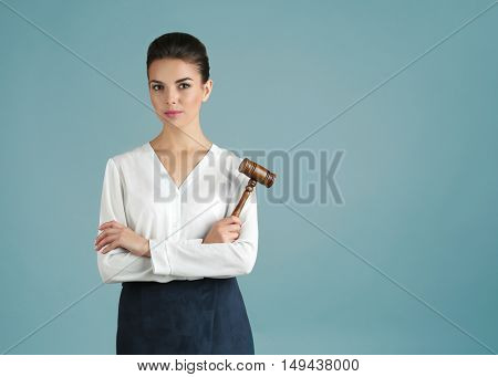 Woman with judge gavel on gray background