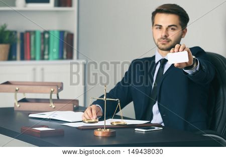 Handsome young man giving business card in modern office