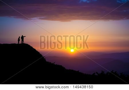 Evening landscape. Silhouettes of two people standing on a rock and looking toward the sun. Sunset in the mountains. Purple light. Summer in the Ukrainian Carpathians. With vignetting effect