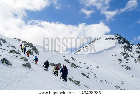 Group of climbers with backpacks going thru snow towards the summit. Sky is clear. High Tatras Slovakia