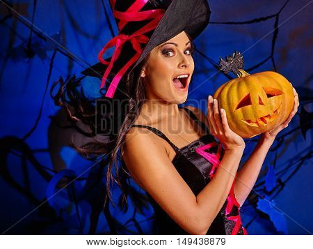 Happy beautiful woman with black long hair wearing witch hat keeps big orange pumpkin on dark halloween background.
