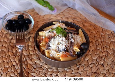 Delicious italian food penne ala puttanesca on a bowl on a table.