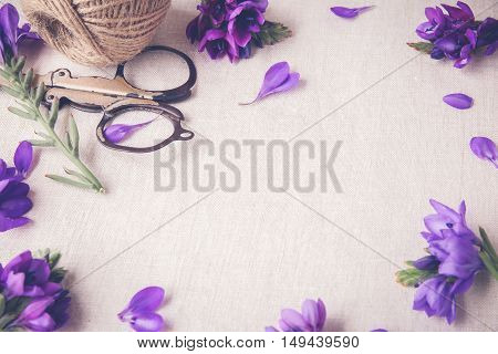 Purple blue flowers craft twine work on linen toning copy space background