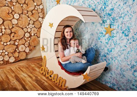 Young Caucasian Mother And Her Baby Boy Sitting On Decorated Moon With Plate Dream