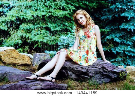 Happy young woman sitting in the park on a sunny summer day. Smiling young woman outdoor. Holiday, vacation.