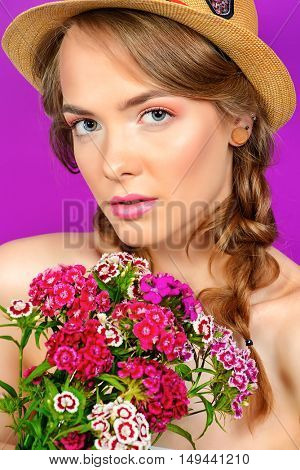 Breath of summer. Romantic girl in a straw hat holds a bouquet of flowers. Beauty, summer fashion.