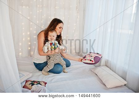 Mother With Baby Boy Sitting On White Bed With Garland