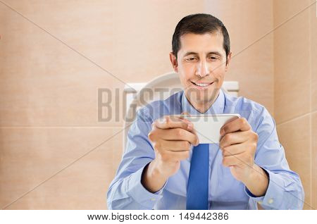 businessman sitting on wc toilet bowl using phone in hands at the bathroom