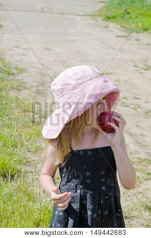 Portrait of a little girl in a summer meadow with decorations of field flowers eating an apple