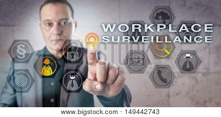 Mature male investigator is activating WORKPLACE SURVEILLANCE onscreen. Information technology metaphor and business concept for monitoring employees for illegal email phone and internet activity.